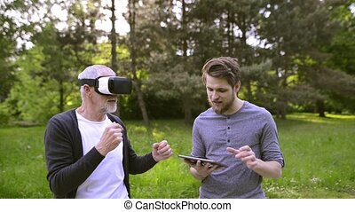Man with tablet and senior father with VR glasses outdoors....
