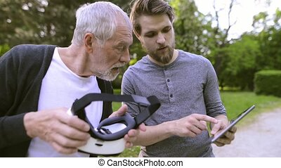 Man with tablet and senior father with VR glasses outdoors.