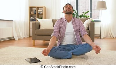 man with tablet computer meditating at home - mindfulness,...