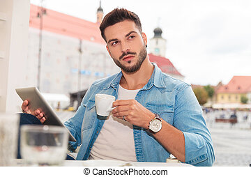 man with tablet having a coffee break in the city