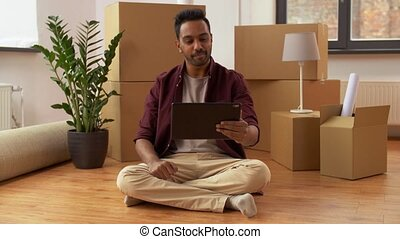 man with tablet pc and boxes moving to new home - moving,...
