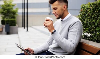 man with tablet pc and coffee on city street bench