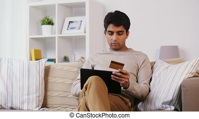 man with tablet pc and credit card on sofa at home -...