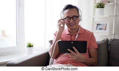 man with tablet pc and headphones at home