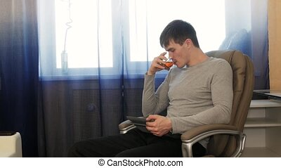 Man with tablet pc sitting on chair, drinking tea