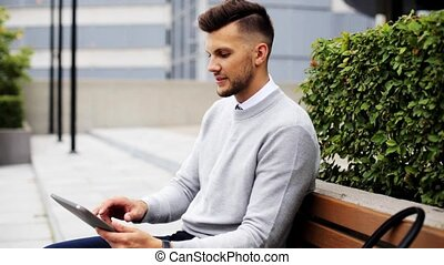 man with tablet pc sitting on city street bench
