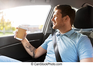 man with takeaway coffee on back seat of taxi car