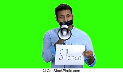 Man with tape on mouth holding megaphone. Young dark-skinned...