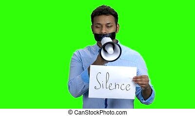 Man with taped mouth trying to speak in megaphone. Green...