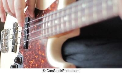 Man with Tatoo playing bass guitar