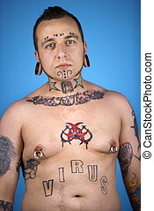 Man with tattoos and piercings. - Barechested Caucasian...