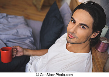 man with tea cup looking into camera from his bed