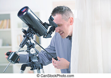Man with astronomical telescope standing near a window