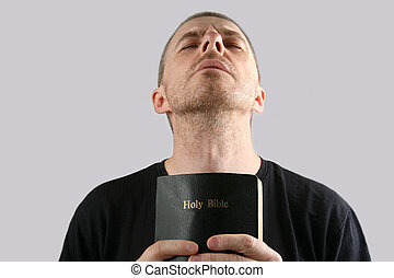 man with the Bible in their hands makes prayer