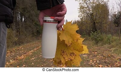 Man with thermos and autumn leaves on road