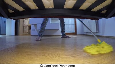 Man with thongs wash the floor under the bed - Man wearing...