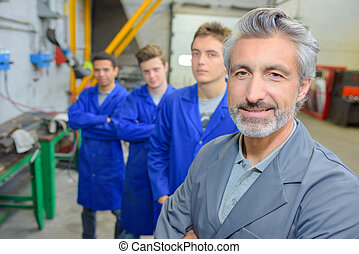 Man with three apprentices stood behind him