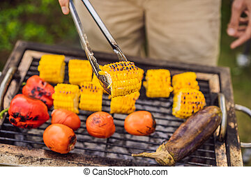 Man with tongs cooking on a back yard barbecue