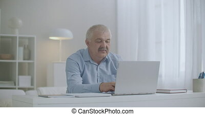 man with toothache is working with laptop in home office, rubbing cheek, sharp pain in teeth or gum, dental diseases, problems with health at working day