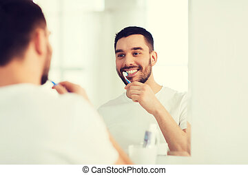 man with toothbrush cleaning teeth at bathroom - health...