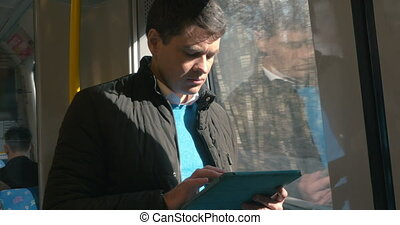 Man with touch pad traveling by train - Young man standing...