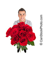 Man with toy bear. Top view of handsome young man holding a bunch of flowers while standing against white background