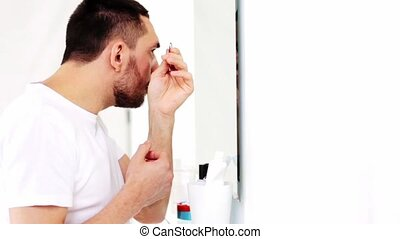 man with tweezers tweezing eyebrow at bathroom - beauty,...