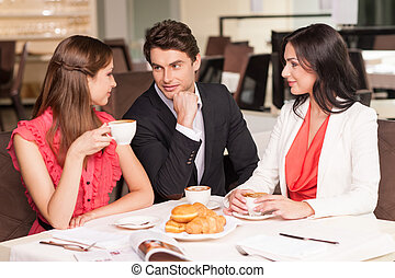 Man with two beautiful women sitting at the restaurant. Talking and drinking coffee