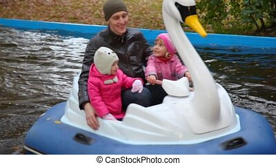 Man with two girls sits in rotating duck in autumn park