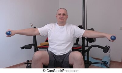 Man with two small dumbbells doing exercise for shoulders