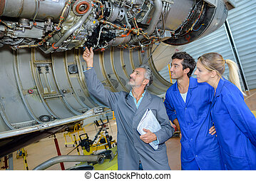 Man with two young people looking at fuselage