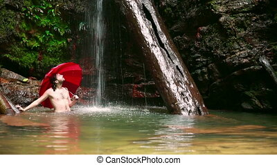 Man with umbrella at waterfall