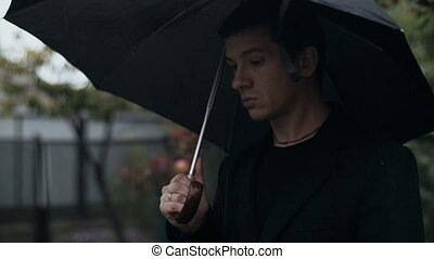 Man with umbrella looking forward at the sky - Sad man with...