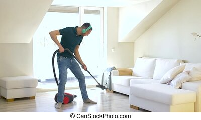 man with vacuum cleaner and headphones at home - household,...