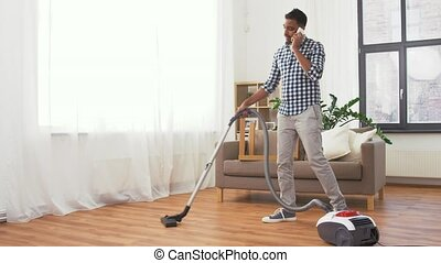 man with vacuum cleaner calling on cell at home - household...