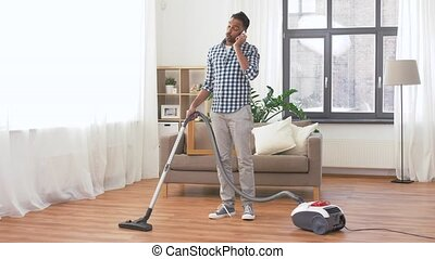man with vacuum cleaner calling on cell at home