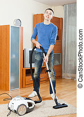 man with vacuum cleaner in living room