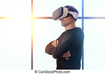 Serious man with black sweater and virtual reality glasses with crossed hands and window at the background with sun
