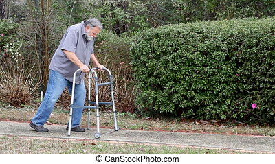 Man With Walker - Disabled man uses a walker to support...