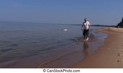 Man with walking poles walk in the water