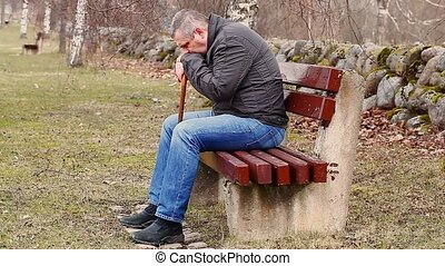 Man with walking stick on bench