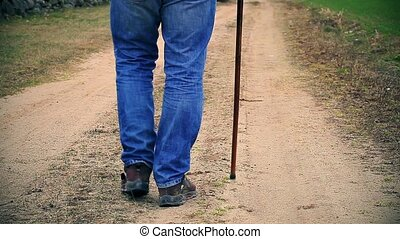Man with walking stick walking away down the road