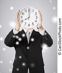 man with wall clock - man covering his face with wall clock