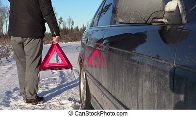 Man with warning triangle near car on the road in winter