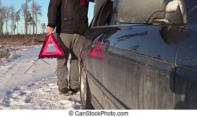 Man with warning triangle walking near car in winter
