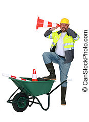 Man with wheelbarrow and traffic cones