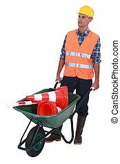 Man with wheelbarrow full of traffic cones