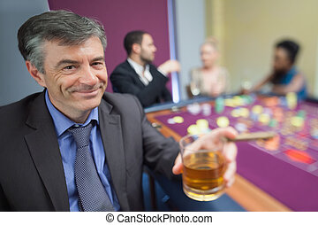 Man with whiskey glass at roulette table