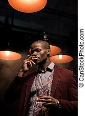 man with whiskey smoking cigar