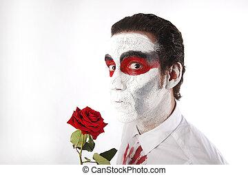 Man with white mascara and bloody shirt holds red rose in ...